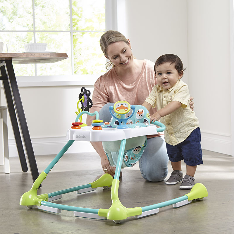 Mom sitting besides the toddler with the Kolcraft walker