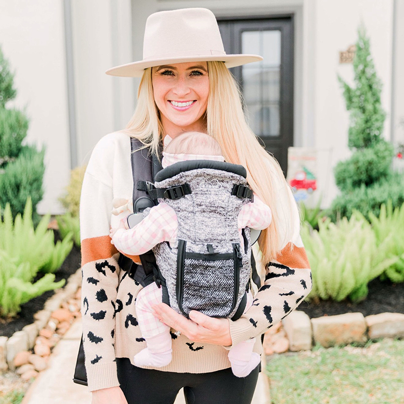 Mom carrying baby in the Kolcraft Cloud Mesh carrier
